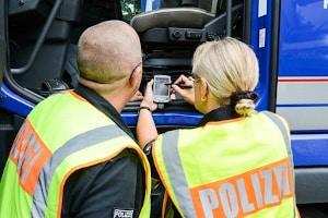 Bei einer Verkehrskontrolle für Lkw-Fahrer wird der Fahrtenschreiber ausgelesen.